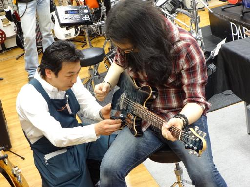 ケリー・サイモンさん島村楽器松本店にてギター担当太田オーダーのSugi Guitars/DS496C 24F 319 EM/ATを試奏。解説中の太田。