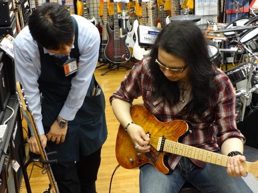 ケリー・サイモンさん島村楽器松本店にて店長花井オーダーのSugi Guitars/DH496M EM/AT AT-MAHO 2Pを試奏。解説中の花井。