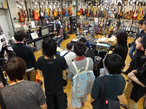 ケリー・サイモンさん島村楽器松本店にて。ケリーさんの演奏を見るお客様でいっぱいです。